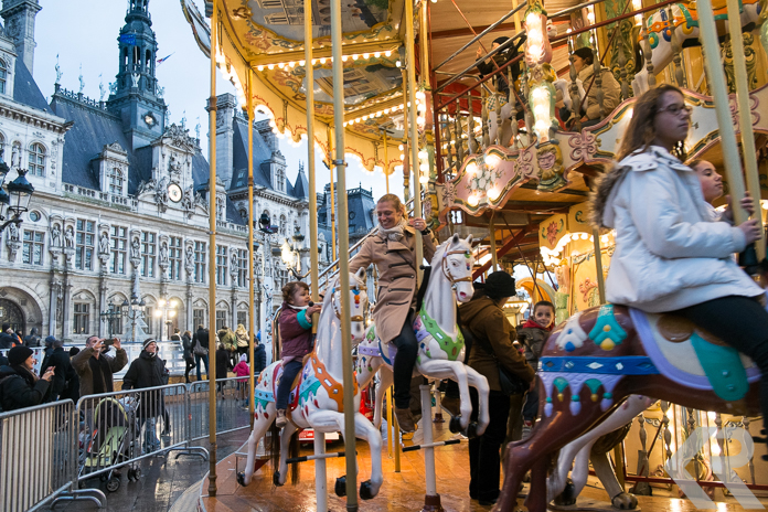 Mother and daughter riding carousel in Paris